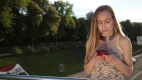 Elegancka kobieta używa smartphone na moscie przy zmierzchem zbiory wideo