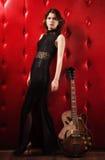 Elegancka kobieta w czerni z gitarą Obrazy Stock
