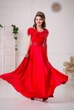 Elegancka kobieta w długiej czerwieni sukni stoi w białym pokoju, d Zdjęcie Royalty Free