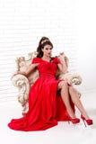Elegancka kobieta w długim czerwieni sukni obsiadaniu na rocznika krześle wewnątrz Zdjęcie Stock