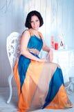 Elegancka kobieta w jaskrawej sukni przy stołem fotografia royalty free