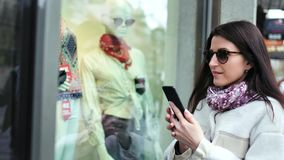 Elegancka kupujący kobieta bierze fotografię atrapa w gablocie wystawowej sklepowa moda odziewa używać smartphone zdjęcie wideo