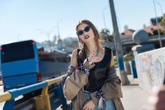 Elegancka młoda kobieta chodzi ulicznego jest ubranym beżowego okopu żakiet zdjęcia stock