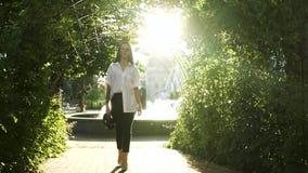 Elegancka młoda kobieta chodzi w parku przy fontanny tłem przy szpilkami zbiory wideo