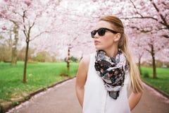 Elegancka młoda kobieta pozuje przy wiosny okwitnięcia ogródem. Zdjęcia Royalty Free
