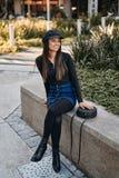 Elegancka młoda kobieta w eleganckim stroju obsiadaniu przy parkiem obraz stock