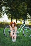 Elegancka młoda kobieta z bicyklem w parku Dziewczyna cieszy się dzień na rowerze zdjęcie royalty free
