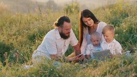 Elegancka młoda kobieta z długie włosy wraz z brodatym mężem i dwa małymi chłodno dziećmi ogląda wideo na a zdjęcie wideo