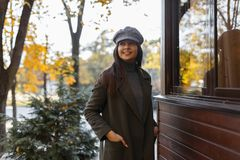 Elegancka młoda piękna kobieta z uśmiechem w rocznika kapeluszu z zielonym żakietem w parku blisko drewnianego budynku zdjęcia royalty free