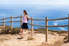 Elegancka młodej kobiety pozycja przy krawędzią skała i gapić się w odległość bardzo Obrazy Royalty Free