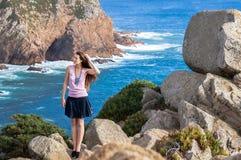 Elegancka młodej kobiety pozycja przy krawędzią skała i gapić się w odległość bardzo Fotografia Royalty Free
