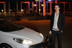 Elegancka młody człowiek pozycja obok jego białego kabrioletu nightlife Biznesmen w kostiumu w luksusowym samochodzie obrazy royalty free