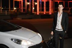 Elegancka młody człowiek pozycja obok jego białego kabrioletu nightlife Biznesmen w kostiumu w luksusowym samochodzie zdjęcie stock