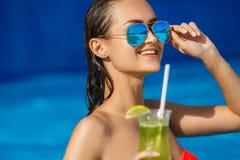 Elegancka młoda kobieta w basenie z koktajlem Obrazy Royalty Free