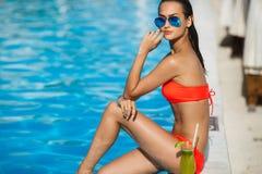 Elegancka młoda kobieta w basenie z koktajlem Fotografia Stock