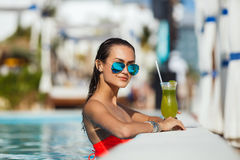 Elegancka młoda kobieta w basenie z koktajlem Obrazy Stock