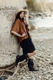 Elegancka modniś kobieta w kapeluszu i krana poncho pozować boho trav Obrazy Stock