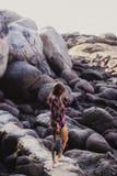 Elegancka modniś kobieta w w kratkę koszula i koszula na lecie wyrzucać na brzeg przy zmierzchem Ścieżka w skały przy plażą Fotografia Stock