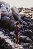 Elegancka modniś kobieta w w kratkę koszula i koszula na lecie wyrzucać na brzeg przy zmierzchem Ścieżka w skały przy plażą Fotografia Royalty Free