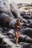 Elegancka modniś kobieta w w kratkę koszula i koszula na lecie wyrzucać na brzeg przy zmierzchem Ścieżka w skały przy plażą Zdjęcie Royalty Free