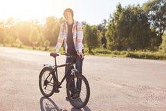 Elegancka modnisia faceta pozycja blisko jego bicyklu podczas gdy mieć odpoczynek po długiej wycieczki, pozujący przy kamerą, cie Obrazy Royalty Free