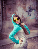 Elegancka nastoletnia dziewczyna w kolorowych okularach przeciwsłonecznych pozuje blisko graffiti obrazy stock