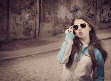 Elegancka nastoletnia dziewczyna w kolorowych okularach przeciwsłonecznych pozuje blisko graffiti obrazy royalty free