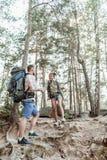 Elegancka nowożytna para wydaje weekend wycieczkuje w lesie z turystycznymi plecakami zdjęcia stock