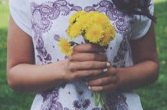 Elegancka oliwkowa dziewczyna trzyma wiązkę żółci dandelions obraz royalty free