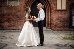 Elegancka pary małżeńskiej pozycja i ono uśmiecha się w tle stary budynku łuk zdjęcia royalty free