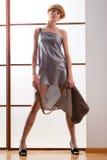Elegancka piękna blondynki kobieta pozuje w studiu, jest ubranym modną suknię Obrazy Royalty Free