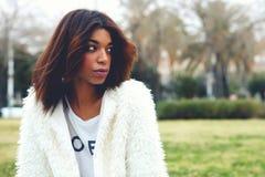 Elegancka piękna młoda dziewczyna siedzi w parku z ekspresyjnymi oczami Obrazy Stock