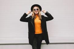 Elegancka rozochocona uśmiechnięta młoda kobieta ma zabawę w mieście na szarość fotografia royalty free