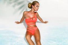 Elegancka seksowna kobieta w bikini na garbnikuj?cym szczup?ym i foremnym ciele pozuje blisko p?ywackiego basenu Sunbathing p?ywa zdjęcia royalty free