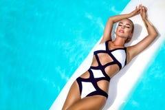 Elegancka seksowna kobieta w luksusowym bikini na garbnikującym szczupłym i foremnym ciele pozuje blisko basenu Sunbathing Obok obraz stock