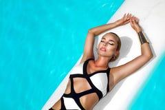 Elegancka seksowna kobieta w luksusowym bikini na garbnikującym szczupłym i foremnym ciele pozuje blisko basenu Sunbathing Obok fotografia royalty free