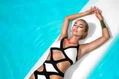 Elegancka seksowna kobieta w luksusowym bikini na garbnikującym szczupłym i foremnym ciele pozuje blisko basenu Sunbathing Obok zdjęcie stock