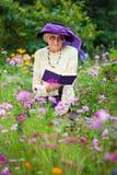 Elegancka starsza kobieta czyta outdoors Zdjęcia Royalty Free