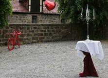 Elegancka stołowa dekoracja z candlestick i czerwień bicyklem w tle, czerwone balonowe komarnicy daleko od obrazy royalty free