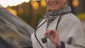 Elegancka w średnim wieku kobieta pokazuje samochodu klucz, szczęśliwy auto właściciel, przewieziony zakup zdjęcie wideo