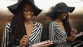 Elegancka wspaniała amerykanin afrykańskiego pochodzenia kobieta w pasiastej koktajl sukni używać jej pastylka komputer zdjęcie wideo
