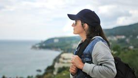 Elegancka wycieczkowicz kobieta w okularach przeciwsłonecznych i nakrętki pozycja na szczycie podziwia pięknego seascape góra zbiory