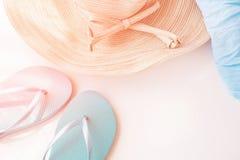 Elegancki Żeński Słomianego kapeluszu kapci plaży Błękitny opakunek na Białego tła Złotych menchiach Migocze Pastelowych kolorów  Fotografia Stock