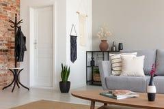 Elegancki żywy pokój z popielatą leżanką i drewnianym stołem, istna fotografia zdjęcie royalty free