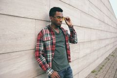 Elegancki afrykański mężczyzna jest ubranym czerwoną szkockiej kraty koszula, okulary przeciwsłoneczni pozuje na miasto ulicie, s zdjęcia stock