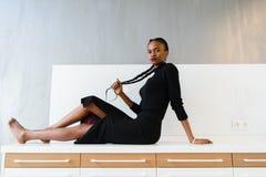 Elegancki afrykanin lub czarna amerykańska kobieta w zmroku smokingowy pozować na biurku w lekkim wnętrzu Fotografia Stock