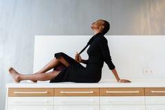 Elegancki afrykanin lub czarna amerykańska kobieta w zmroku smokingowy pozować na biurku w lekkim wnętrzu Obraz Royalty Free