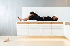 Elegancki afrykanin lub czarna amerykańska kobieta w zmroku smokingowy pozować na biurku w lekkim wnętrzu Zdjęcia Stock