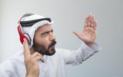 Elegancki Arabski mężczyzna w hełmofonach, Arabski facet słucha muzyka obrazy royalty free