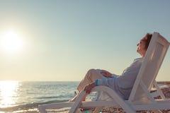 Elegancki atrakcyjny dojrzały kobiety 50-60 lat siedzi w Dec zdjęcia stock
